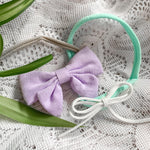 Two handmade baby bow headbands - one purple on a soft nude nylon cord, and a second smaller white bow on a teal nylon band. Ethically and locally made in Kitchener, Ontario