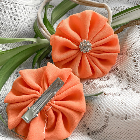 Fabric pinwheel flower hair bows for babies and toddlerswith a gemstone in the middle. A light creamsicle orange colour. Ethically and locally made in Kitchener, Ontario