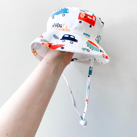 A white cotton sunhat with built-in UV protection with a red and blue truck pattern
