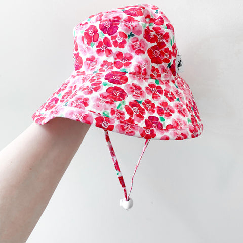 A cotton sunhat with a pink floral print and a wide brim. Handmade in Canada from Puffin Gear