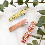 Three baby and toddler hair clips: gold, rose gold, and pink confetti glitter