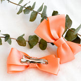 Two locally made peach baby and toddler bow clips