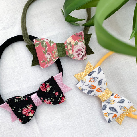 Three floral bows on nylon headbands for babies and toddlers