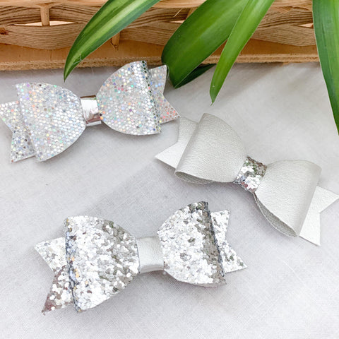 Three silver bow clips for babies and toddlers. Two glittery, one shiny, but each slightly different.