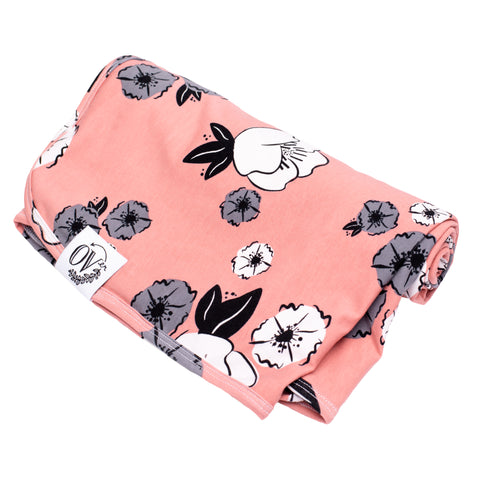 A bright pink baby blanket with grey, white, and black flowers. Perfect for swaddling. Ethically handmade in Canada