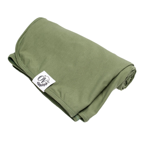 A solid green swaddle blanket that was ethically handmade in Canada
