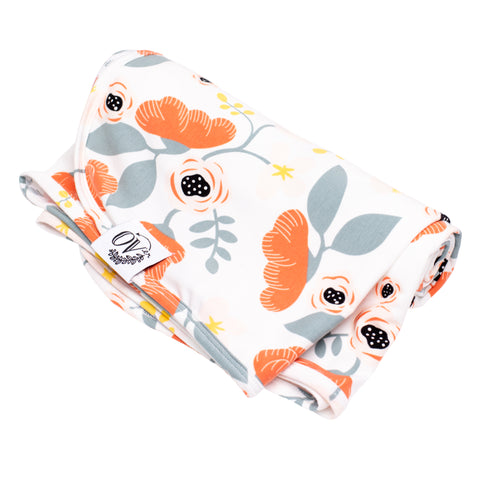 A white swaddle blanket with pinkish red poppies and light blue leaves from the over company