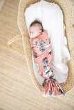 A baby sleeping while swaddled in the pink floral butter blanket from the OVer company. Handmade in Canada