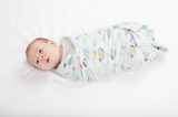 A newborn baby wrapped in the Canadian hot air balloon swaddle blanket