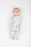 A baby boy wrapped in the hot air balloon swaddle blanket made from eco friendly cotton and bamboo