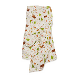 A soft, eco-friendly swaddle blanket featuring light brown woodland animals and green trees on a light cream background