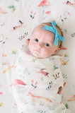 A baby girl swaddled in the soft, eco friendly bamboo and cotton swaddle blanket