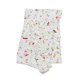 A soft, eco friendly swaddle blanket with woodland animals, mushrooms, plants, and gnomes on a white background