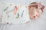 A baby girl sleeping while swaddled in the eco friendly, Canadian swaddle blanket