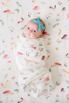 A baby girl swaddled in the woodland gnome swaddle blanket
