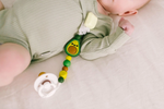 Baby wearing an avocado pacifier clip to hold their soother.