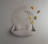 A gender neutral silicone bib that catches food as it falls.