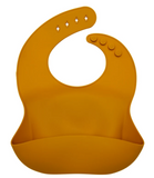 A silicone catch all bib in a deep yellow / mustard colour. It has a pouch at the bottom to catch food baby drops