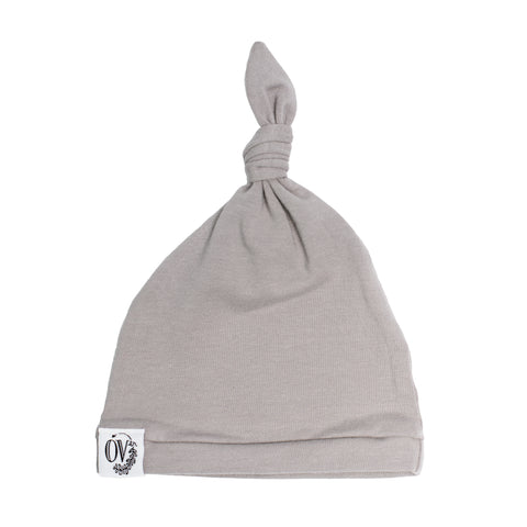 A plain grey baby hat with an adjustable knot at the top