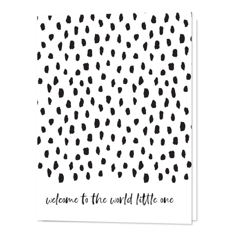 "A handmade white card with black dots. Along the bottom is written ""welcome to the world little one"" in script"