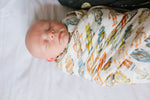 Baby boy swaddled in vintage robot swaddle made with eco friendly bamboo. Baby shower