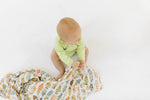 Baby boy playing with vintage robot swaddle