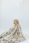 Baby boy playing with soft muslin vintage robot swaddle for baby shower