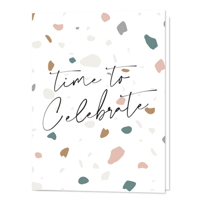 "A white card from the OVer Company that says ""Time To Celebrate"" on the front. It has a terrazo pattern with pink and green specks. Gender Neutral."
