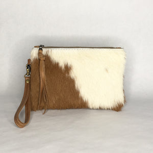 Handmade brown and white cowhide clutch with leather wristlet strap by Marge and Rudy