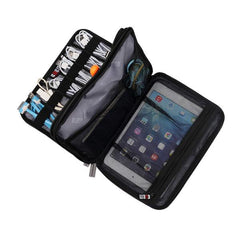 Black travel electronics organizer with showcasing the many compartments to house cables, cords, and an ipad when traveling. Photo by plentiful travel, travel products.