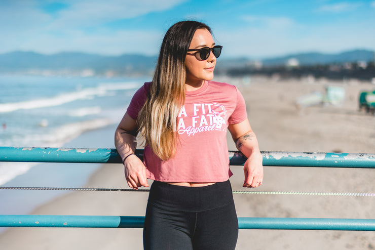 Millenial female at the beach wearing Kinda Fit Kinda Fat premium mauve cropped top.