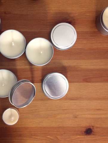 aerial of candles in tins on wooden table