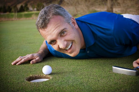 a man on a putting green close to the hole