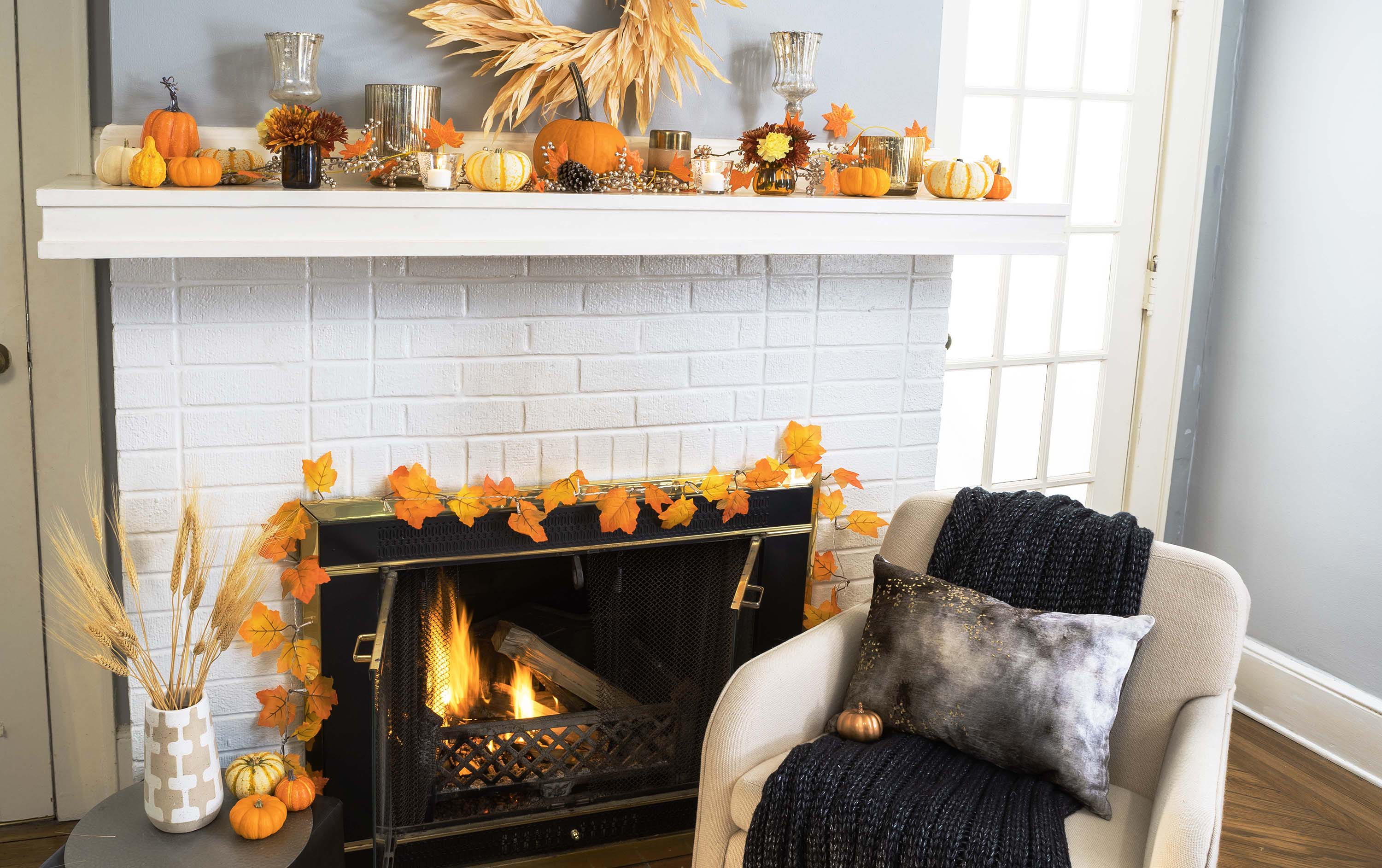 a fireplace mantel with darker fall decorations