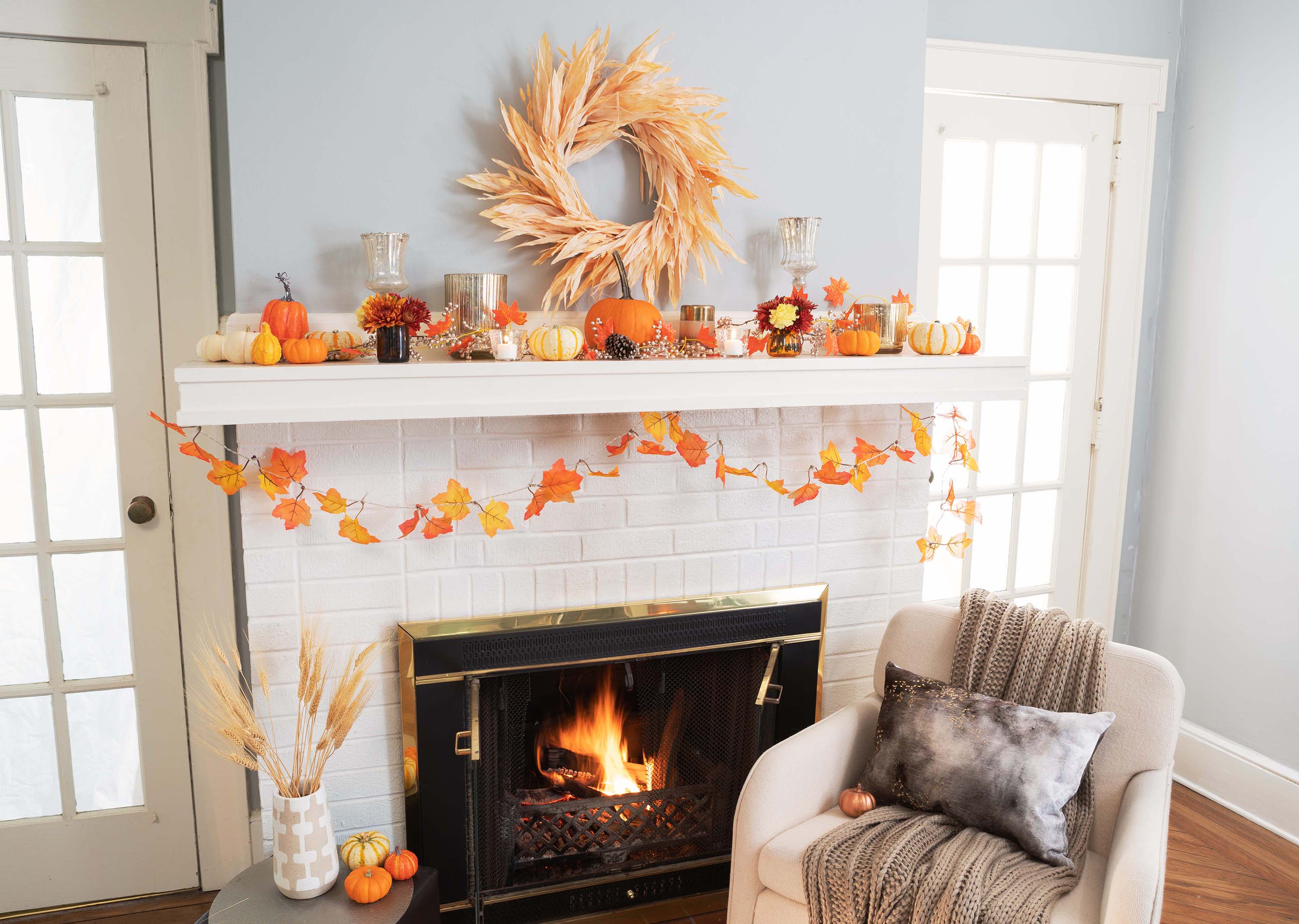 A fireplace mantel with fall decorations
