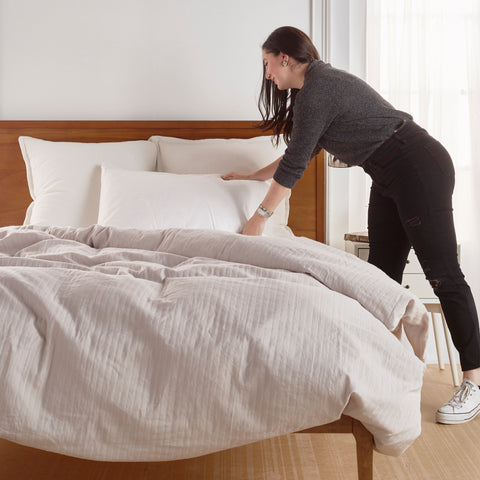 woman making a bed in a modern bedroom