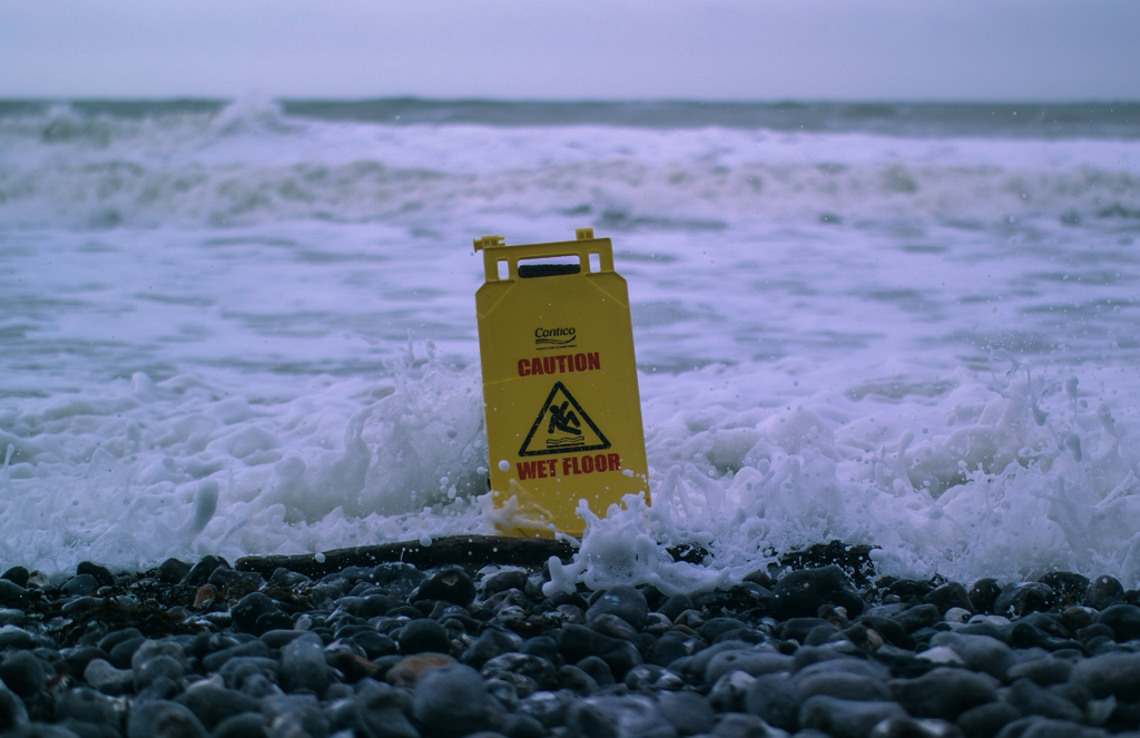 Caution wet floor (house or office cleaning sign) placed by waves from the sea