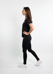 "Woman wearing black motivational PGB Fit fitness T-shirt with black PGB Fit fitness leggings that both say, ""Get Better"""