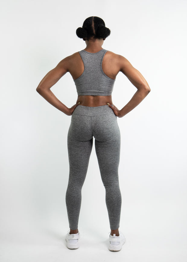 "Woman wearing gray motivational PGB Fit fitness leggings with gray PGB Fit fitness sports bra that both say, ""Get Better"""