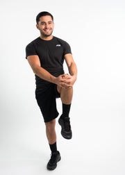"Man wearing black motivational PGB Fit fitness shorts with black PGB Fit fitness T-shirt that both say, ""Get Better"""