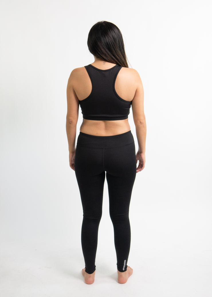 "Woman wearing black motivational PGB Fit fitness leggings with black PGB Fit fitness sports bra that both say, ""Get Better"""