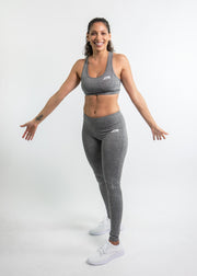 "Woman wearing gray motivational PGB Fit fitness sports bra with gray PGB Fit fitness leggings that both say, ""Get Better"""