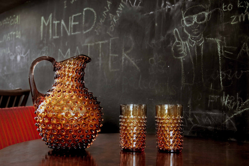 Glass Tumblers alongside Glass Jug standing on the table