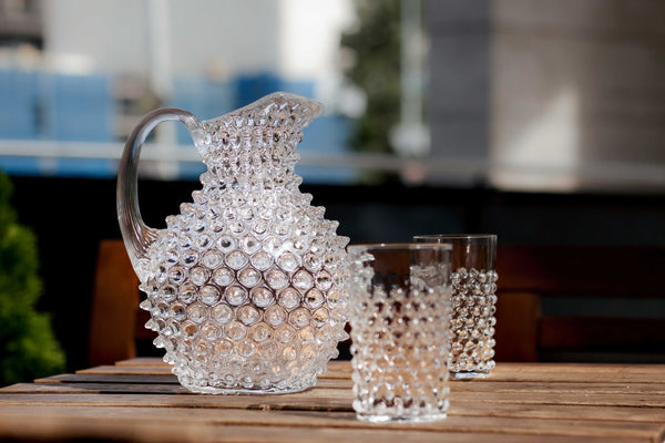 Crystal Hobnail Tumblers with matching pitcher on a wooden table