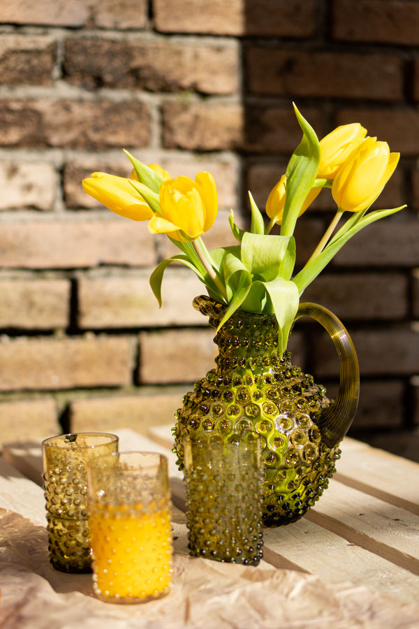 Bonsai Green Bohemian glass jug with yellow tulips and three hobnail tumblers in bonsai green and underlay amber with orange juice