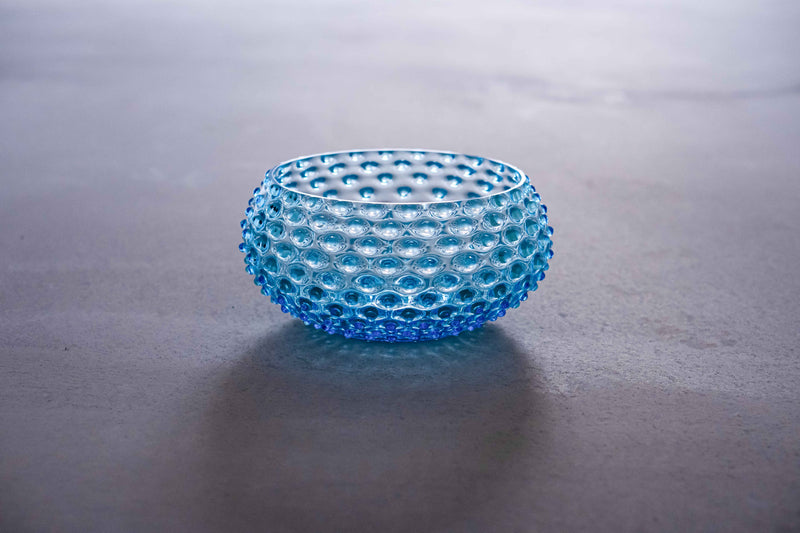 Side view of glass azure bowl on the Ground