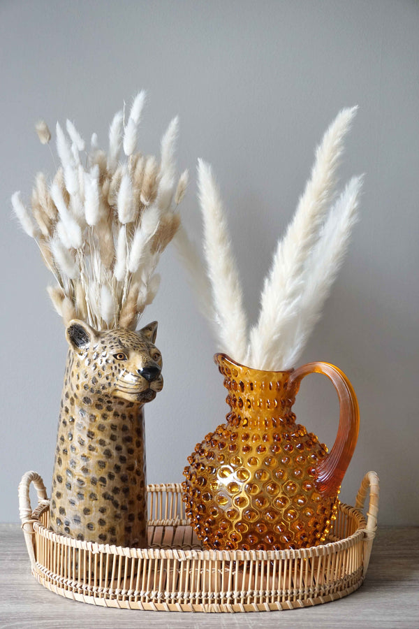 Glass Amber Jug in a Basket next to Cheetah wooden statue