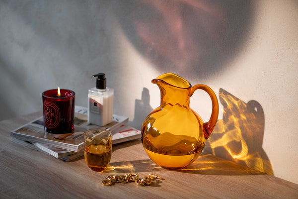 Amber Glass Jug with a matching tumbler on a table with a red candle and a handcream..