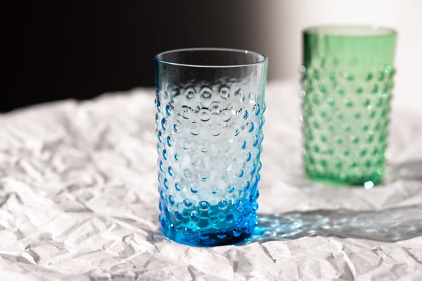 Azure Hobnail Glass on the white paper with Green Tumbler in Background