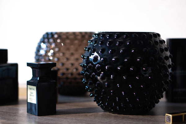 Black Glass Hobnail Vase on the table set with parfumes and another vase